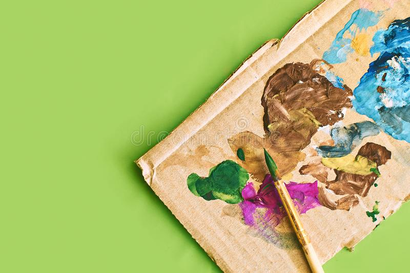 Kartonkaart met vlekken van verf als palet voor het schilderen worden gebruikt en een penseel op lichte verse groene de lentestij stock afbeelding