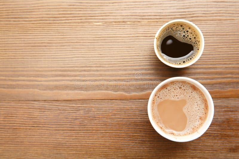 Kartonkoppen van koffie op houten lijst, hoogste mening stock foto's