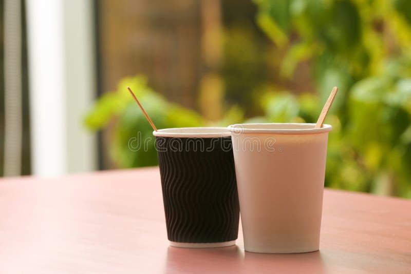 Kartonowi filiżanka kawy na stole przeciw zamazanemu tłu obraz stock