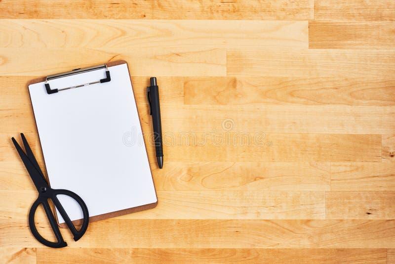 Kartonowy schowek, nożyce i pióro na drewnianym tle, obraz stock