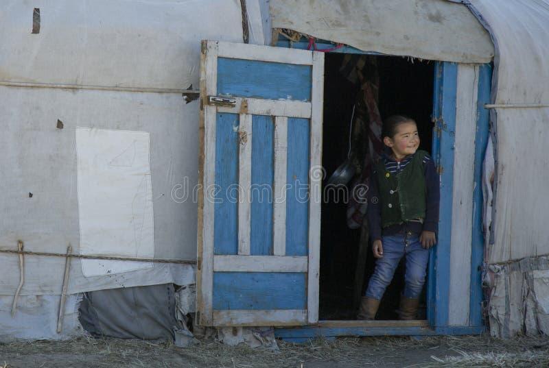 Kasachisches Mädchen, das aus ihr Haupt-yurt herauskommt stockfotografie