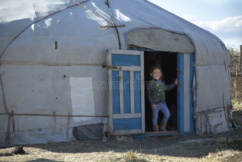 Kasachisches Mädchen, das aus ihr Haupt-yurt herauskommt lizenzfreie stockbilder