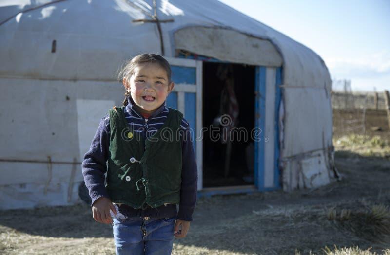 Kasachisches Mädchen, das aus ihr Haupt-yurt herauskommt stockbilder