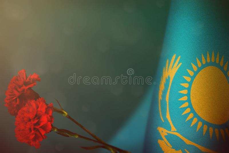 Kasakhstan flagga för heder av veteran eller minnesdagen med modellen för två den röda nejlikablommor Härlighet till Kasakhstan h arkivfoton