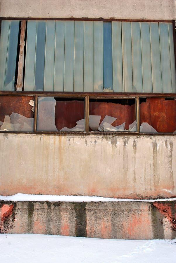 Kasetonuje ścianę zaniechany administracyjny budynek z łamanym szkłem w okno i wsiadającym w górę ośniedziałych metali talerzy z zdjęcia royalty free