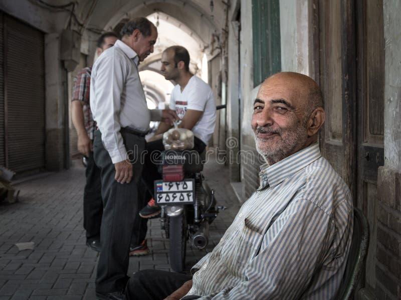 KASHAN, IRÁN - 13 DE AGOSTO DE 2016: Viejo vendedor iraní del huevo que sonríe después de un trato cerrado con la gente iraní com foto de archivo libre de regalías
