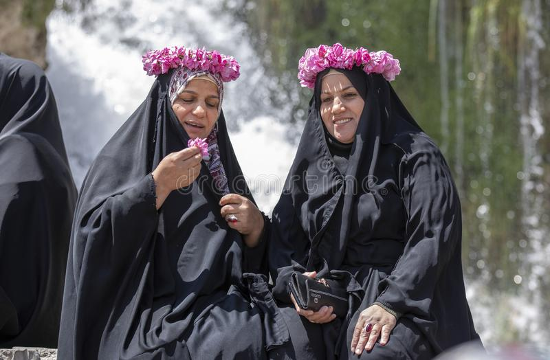 Iranian ladies chatting and having fun. Kashan, Iran, 25th April 2019: iranian ladies with roses decorating their heads resting in front of a waterfall stock images
