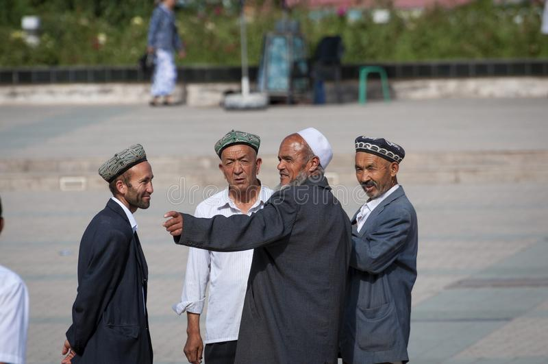 Group of Uyghur man talking in a square in the city of Kashgar, Xinjiang stock image