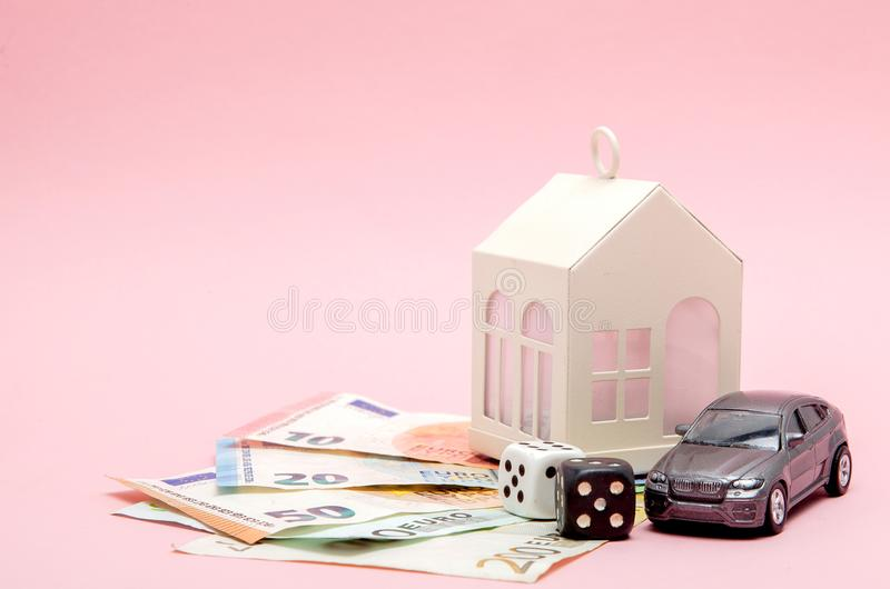 Kasino-, dobbleri- och förmögenhetbegrepp Modellera huset, och bilen, lekar tärnar och europengar på rosa bakgrund med kopierings royaltyfri bild