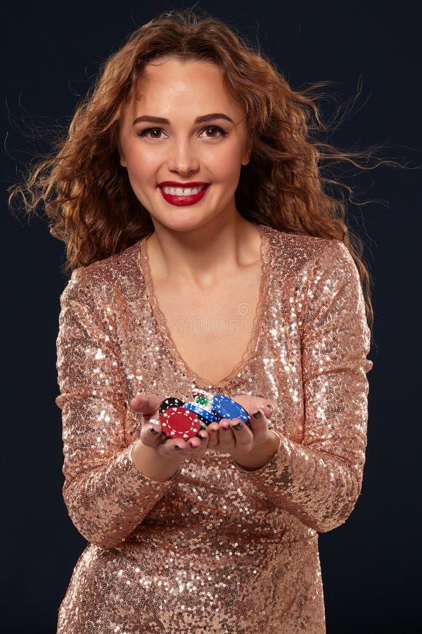 KASINObegrepp St?ende av den unga n?tta caucasian kvinnan som spelar i kasino Roulett pokerchiper, kort, hjul som ?r svart arkivfoton