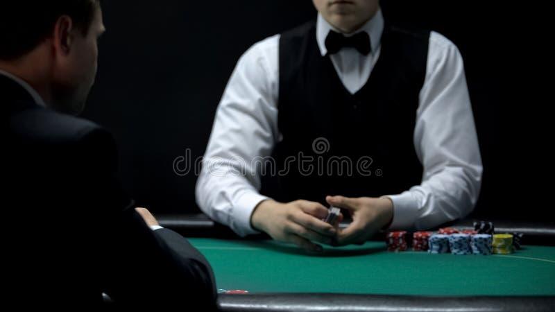 Kasinokunden-WarteCroupier, zum von Karten, Möglichkeit zu behandeln, am Pokerspiel zu gewinnen lizenzfreie stockfotografie