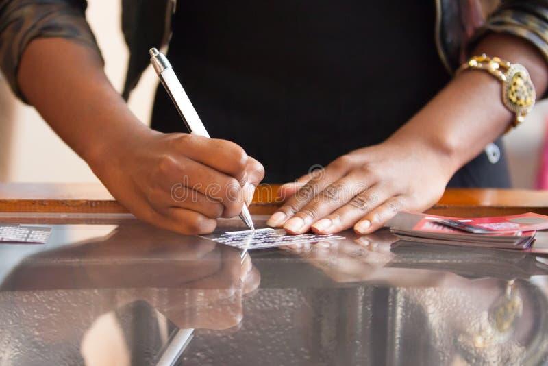 Kasjer przy sklepu writing na dyskontowej karcie obrazy stock