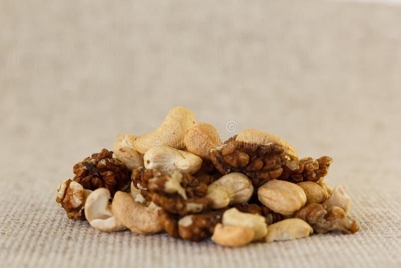 Kasjuer och valnötter är blandade i en hög royaltyfri fotografi