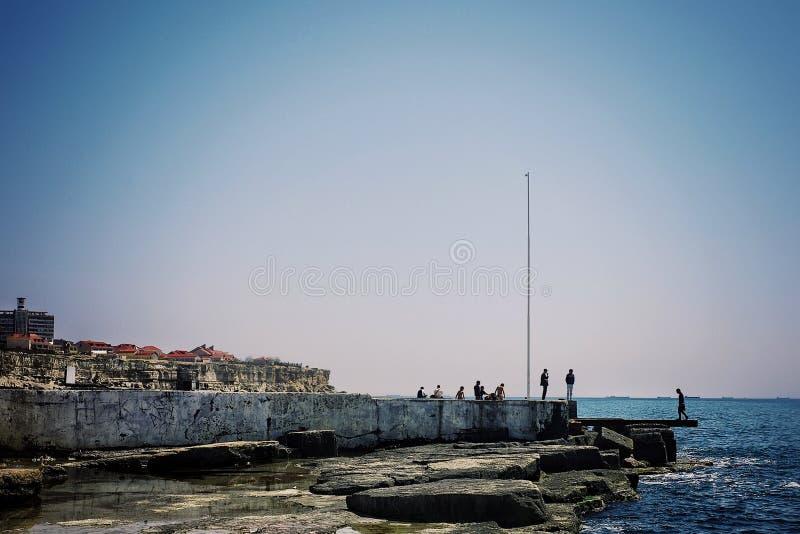 Kaspische overzeese kust met rotsen en de verre gebouwen van de stad royalty-vrije stock afbeelding
