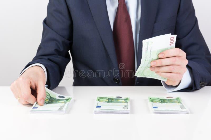 Kassör i bank` s räcker att räkna eurosedlar på tabellen fotografering för bildbyråer