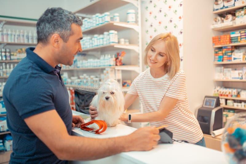 Kassörska som ger den vita fluffiga hunden till hennes ny ägare royaltyfri bild