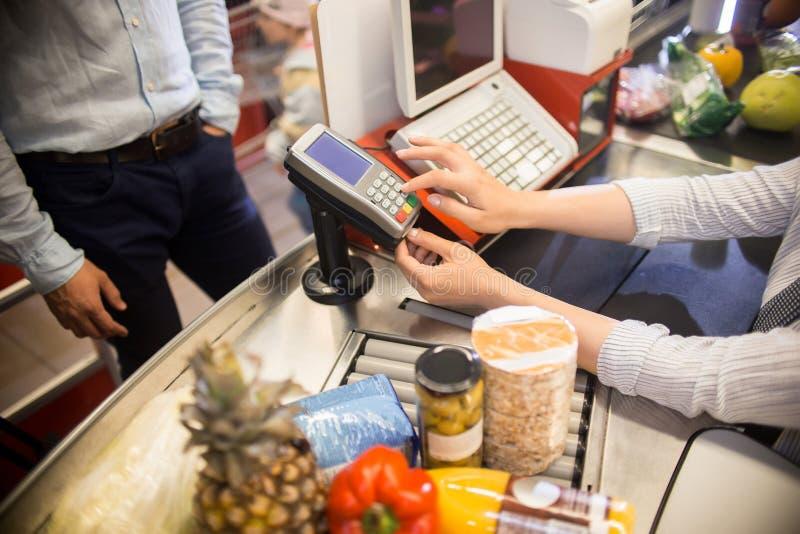 Kassörska Using Payment Terminal i supermarket royaltyfri fotografi