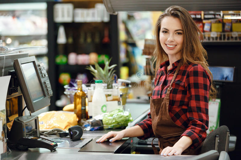 Kassörskadamen på workspace i supermarket shoppar royaltyfri foto