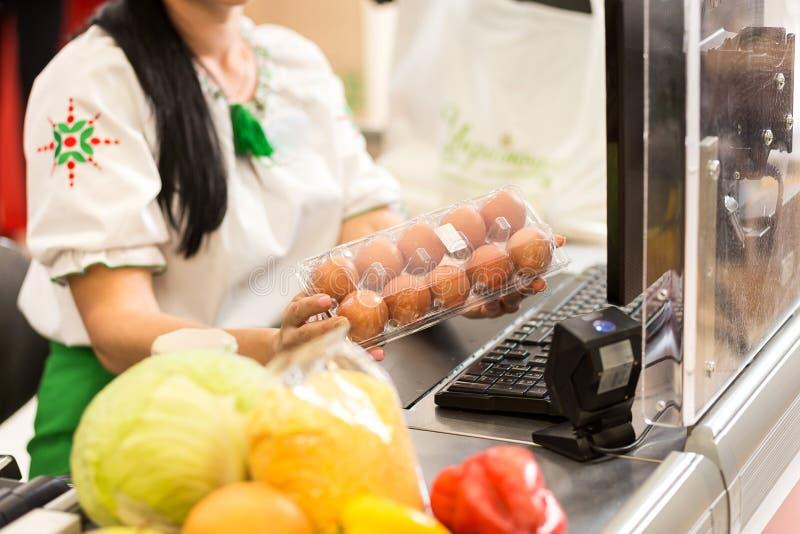 Kassörskan arbetar på supermarket royaltyfri bild