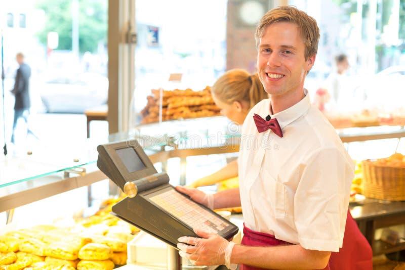 Kassörskan i bagare shoppar att posera med kassaapparaten arkivbilder
