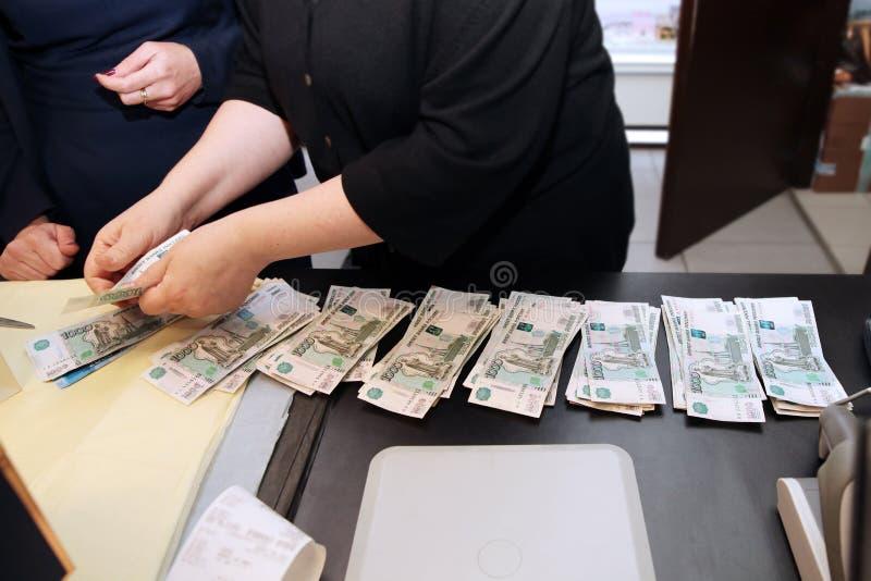 Kassörskan räknar pengarna, en packe av sedelvärde tusen rubel och ger dem moscow 22 11 2018 royaltyfria bilder
