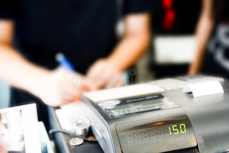 Kassörskaräknaren i supermarket, kassörska på en supermarket checkout i ett varuhus arkivfoton