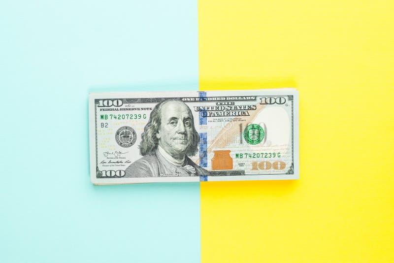 Kassa för pengar för räkning för US dollar 100 på blå och gul bakgrund Hög av hundra amerikanska dollar sedel royaltyfria bilder