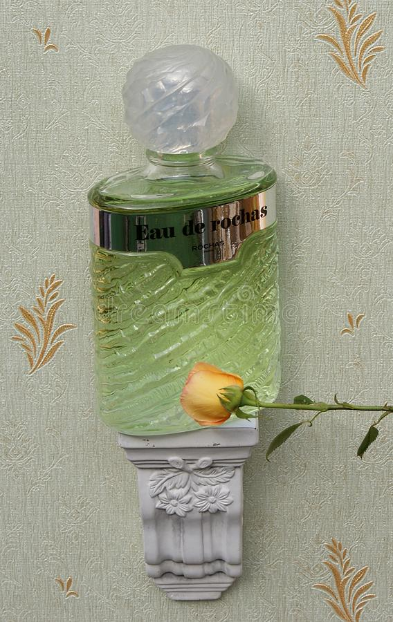 Eau de Rochas, fragrance for ladies, large perfume bottle on an antique wall console with ornament decorated with an English rose royalty free stock images