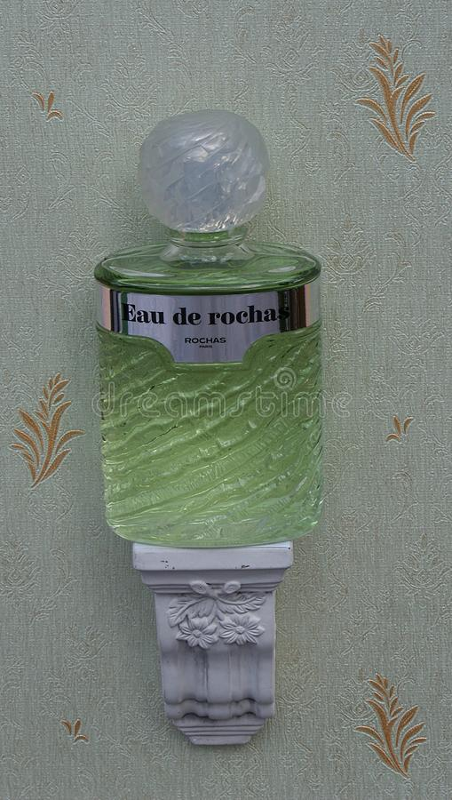 Eau de Rochas, fragrance for ladies, large perfume bottle on an antique wall console with ornament royalty free stock image