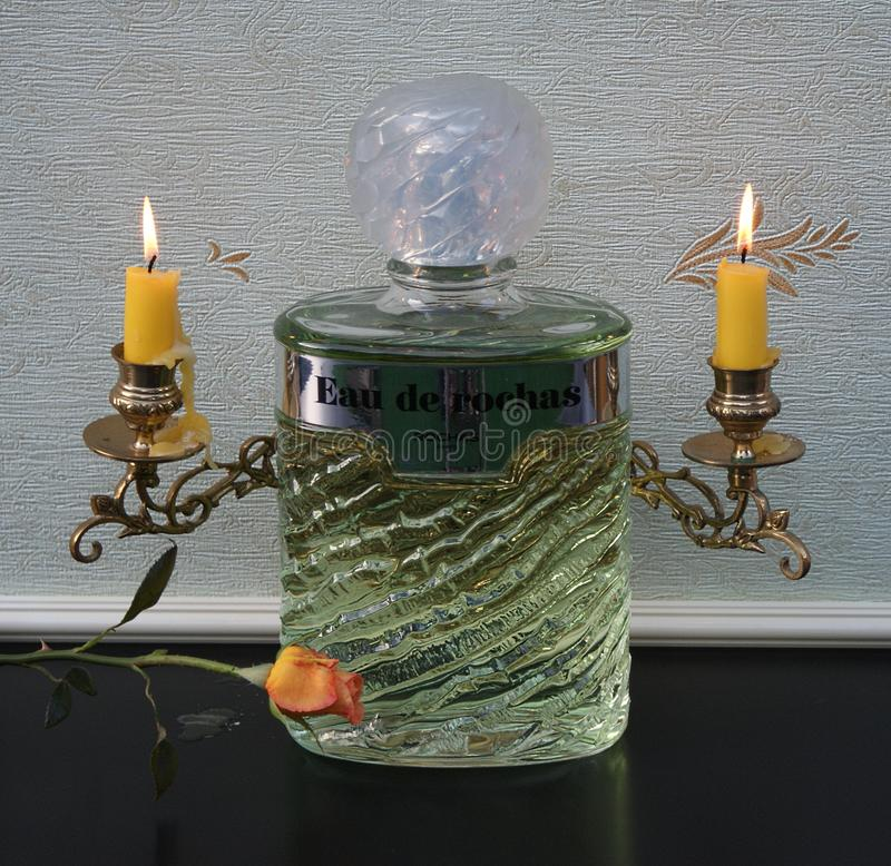 Eau de Rochas, fragrance for ladies, large perfume bottle in front of a candelabra with shining candles decorated with a rose stock images