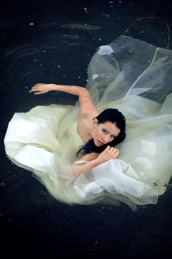 Kassera klänningen. Bruden tar på ett bad i hennes bröllopsklänning arkivbild