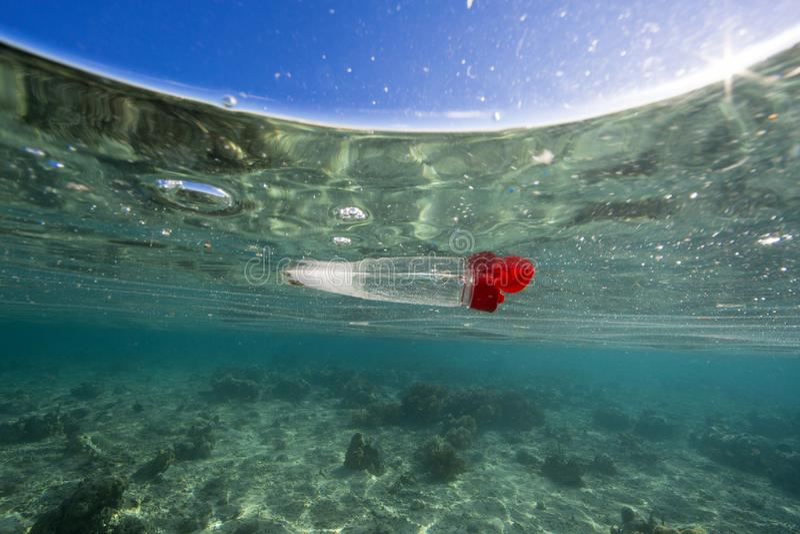 Kasserad plast- flaska som svävar i havet över korallreven royaltyfri foto