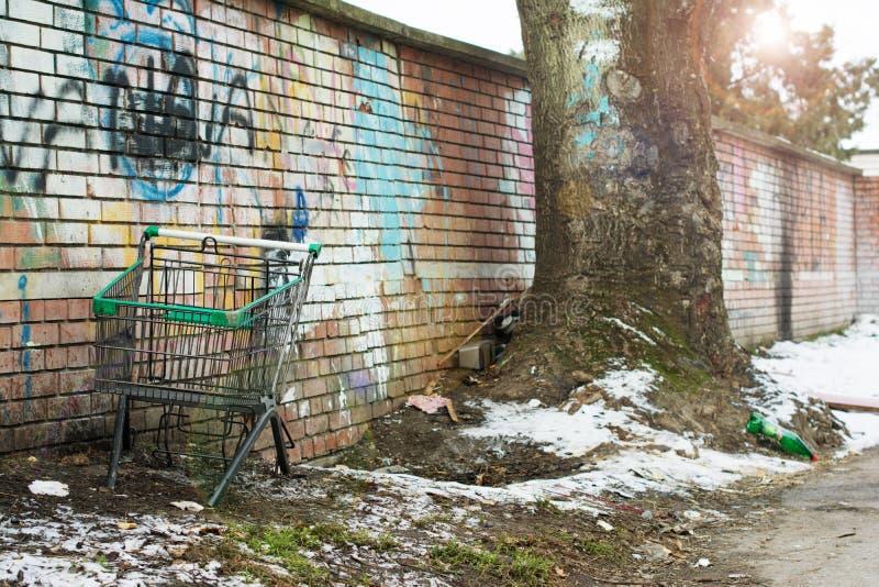 Kasserad shoppa vagn utan hjul som står vid en naken vägg arkivfoto