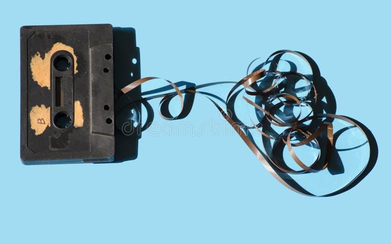 Kassett på ett kulört bakgrundsljus - blått retro arkivbild