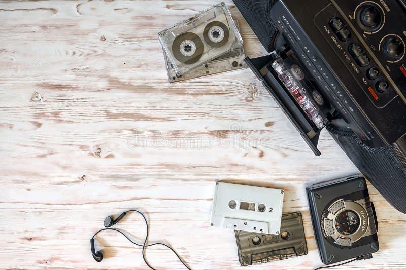 Kassettspelare, kassettregistreringsapparat och ljudband på trälodisar arkivfoton