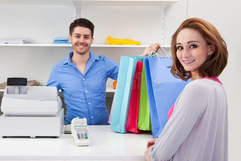 Kassier het overhandigen het winkelen zak aan klant stock afbeelding