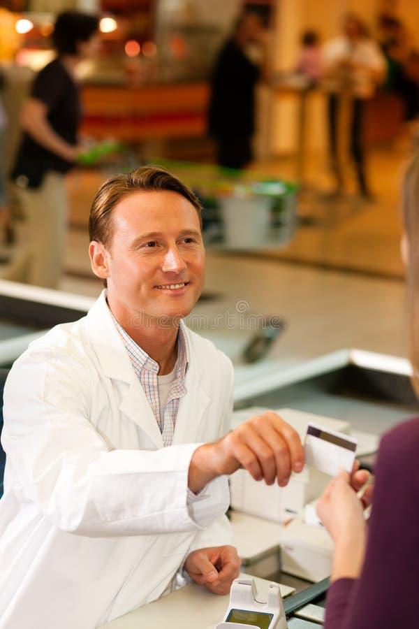 Kassier in supermarkt die creditcard neemt stock afbeeldingen