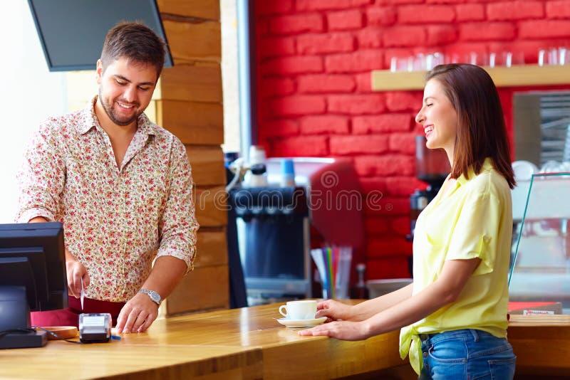 Kassierer dient Kunden am Bargeldschreibtisch im Café lizenzfreie stockfotos