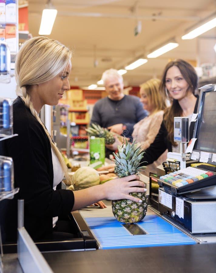 Kassierer-Making Bills While-Kunden, die an der Prüfung Counte stehen stockbilder