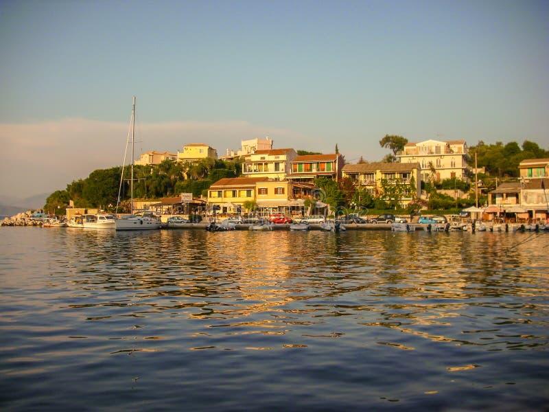 Kassiopi Korfu, Grekland - Juni 07 2013: Härlig solnedgång av fartyget som ansluter område i Kassiopi, Korfu, Grekland fotografering för bildbyråer
