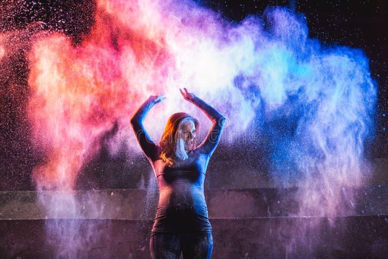 Kast för ung kvinna färgar pulver på mörk bakgrund royaltyfri bild