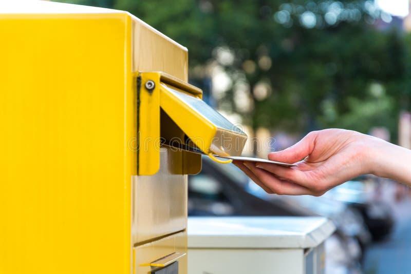 Kasta en bokstav i en gul brevlåda royaltyfri foto