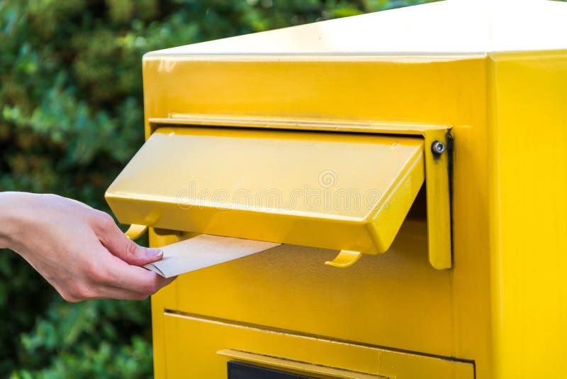 Kasta en bokstav i en gul brevlåda royaltyfria bilder