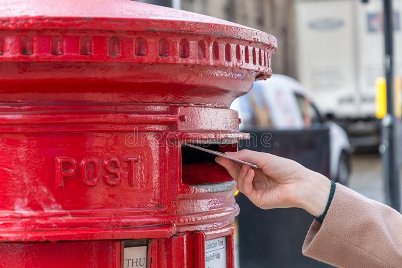 Kasta en bokstav i en röd brittisk stolpeask arkivfoto