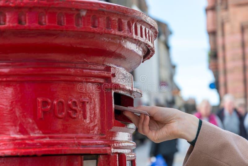 Kasta en bokstav i en röd brittisk stolpeask royaltyfria bilder