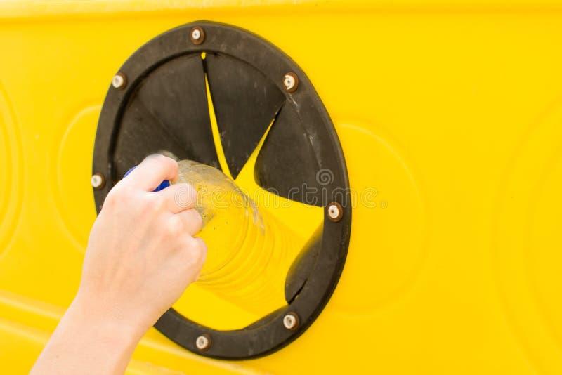 Kasta en flaska in i återvinningbehållaren royaltyfri foto