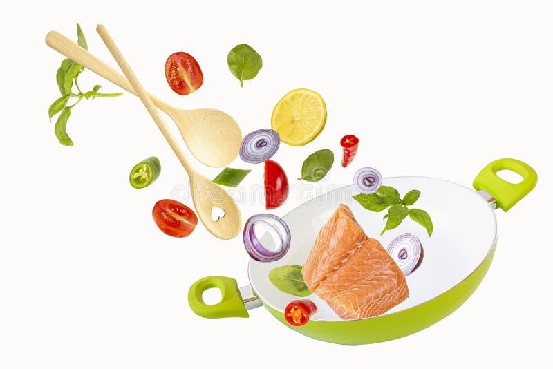 Kasta fisken och grönsakerna med kryddor in i den gröna stekpannan Isolerade objekt p? vit bakgrund Flygmat arkivfoto