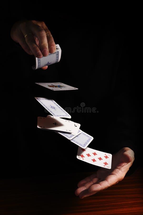 Kasta kort från en hand till annan mot en svart backgr royaltyfria foton