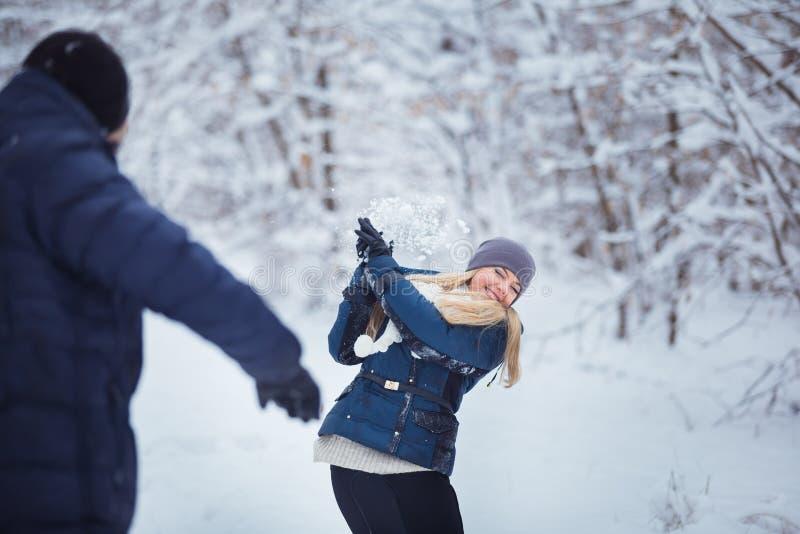 Kasta snöboll slagsmål Övervintra par som har gyckel att leka i snow utomhus Unga joyful kopplar ihop royaltyfria bilder