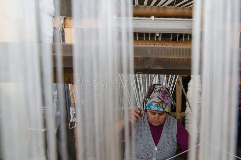 Traditional hand weaving in the Kastamonu in Turkey. Kastamonu,TURKEY-November 05,2017: Woman working at the loom. Turkey national crafts. Focused on the woman royalty free stock image